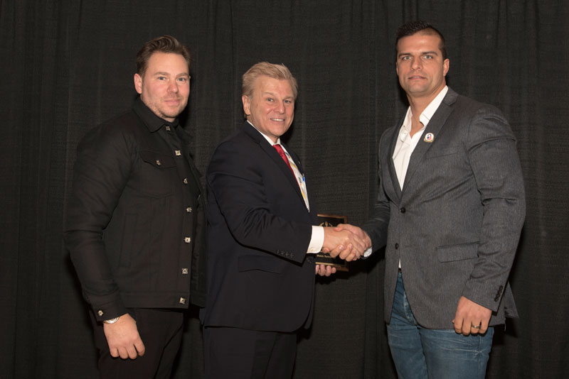 On hand to accept TerrorMate's 'ASTORS' awards were Jaromy Jannard-Pittario, (at left), and Barry Oberholzer, Founder of TerrorMate, (at right), being presented the honor by AST's publisher.