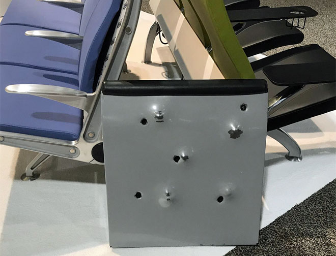 The image shown is a seat-back from airport seating manufactured by Arconas Corp. This style of seating (the 'Flyaway') is in use at every American Airlines gate system-wide. The damage shown resulted from handgun rounds (9mm and 44mag) fired from opposing directions. Inspection reveals no penetration of Amulet® ballistic barrier.