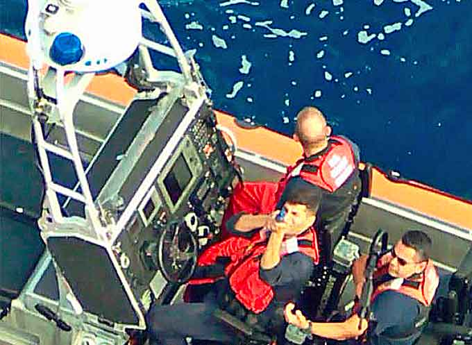 A Coast Guard boat with people carrying simulated weapons.(Courtesy of the USCG)