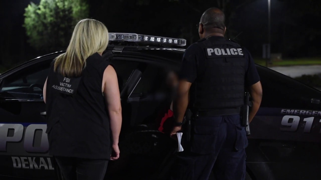 An FBI victim specialist and a DeKalb County (Atlanta) Police Department officer interview a woman in a police cruiser during Operation Independence Day, a monthlong nationwide operation to find human traffickers and rescue underage trafficking victims. (Courtesy of the FBI)
